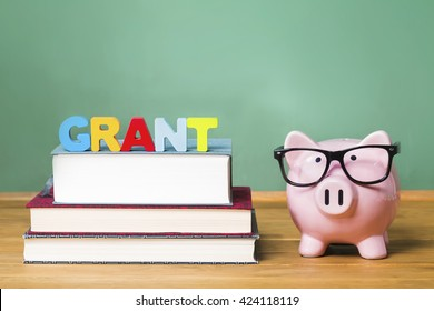 Educational grant theme with pink piggy bank with chalkboard in the background as concept image of the costs of education