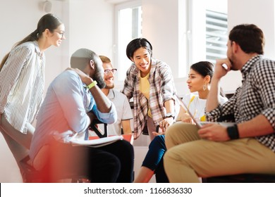 Educational process. Positive emotional young people sitting in a little circle and smiling while having an interesting discussion at the university