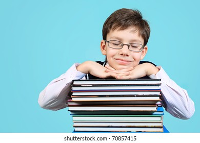 Educational theme: portrait of a schoolboy with books. Over grey background.