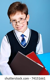 Educational theme: portrait of a schoolboy with books. Studio shot over grey background.