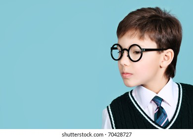 Educational theme: portrait of a schoolboy. Studio shot over grey background.