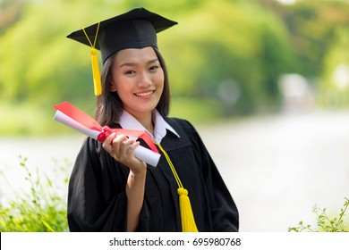 Educational theme.Beautiful woman graduating holding her diploma and smiling in an academic gown.
