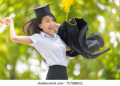 Educational theme.Beautiful woman graduating jumping with holding her diploma and smiling in the park.
