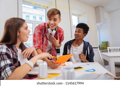 Educational video. Three smart creative students feeling curious while watching educational video