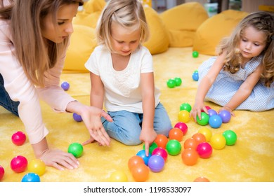 educator gesturing on colored balls to kids in kindergarten, child pointing on one