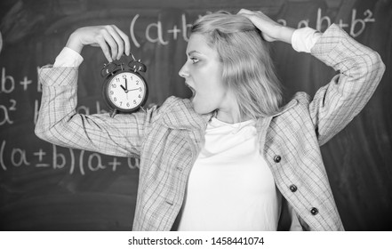 Educator start lesson. She care about discipline. Woman teacher hold alarm clock. Lessons schedule concept. Time for break. Girl wonder about time. Welcome teacher school year. Healthy daily regime.