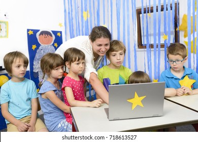 Educator surrounded by  kids at kindergarten using a laptop