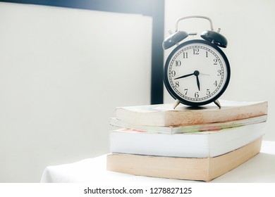 Eduction concept. Alarm clock and book on reading table. Vintage filter