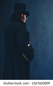 Edwardian man in long black coat and hat holding book standing towards grey wall.