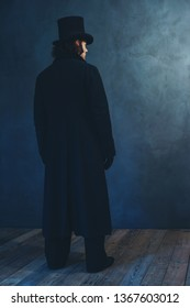 Edwardian man in long black coat and hat standing towards grey wall.