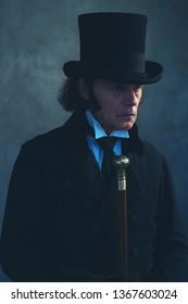 Edwardian man in long black coat and hat holding cane.