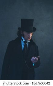 Edwardian man in long black coat and hat holding pocket watch.