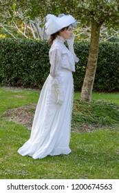 Edwardian woman in white ensemble in garden