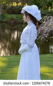 Edwardian woman in white ensemble in garden
