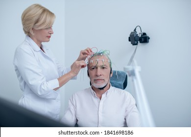 EEG examination. Female neurologist adjusting electrodes on gray-haired male patient head undergoing electroencephalogram