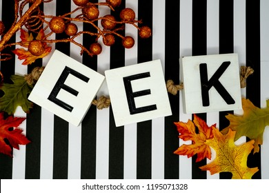 Eek Halloween phrase letters on fun black and white stripe background.  Maple leaves and orange glittery stems for festivity. Useful for Halloween projects and headers