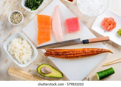 Eel, a knife, salmon, tuna and rockfish on a cutting board. Cucumber, rice, an avocado, a bamboo mat, sesame seeds, gari and ice. Making sushi.