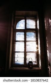 Eerie atmosphere in an abandoned building with huge windows and spider webs and one lamp. Halloween themed image.