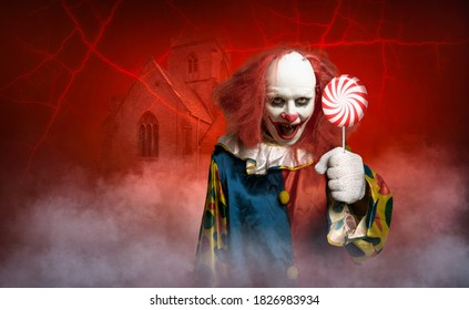 an eerie clown in front of a red background tries to lure with a lolly