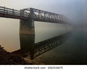 Eerie image of truss footbridge over the lake fading into the fog during the early morning at Tims Ford State Park in Winchester Tennessee