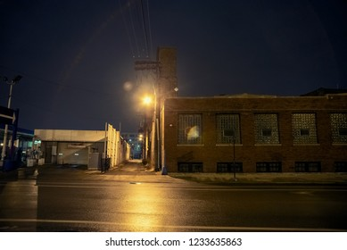 Eerie industrial urban street city night scene with a vintage factory warehouse and a scary alley next to a retro gas station