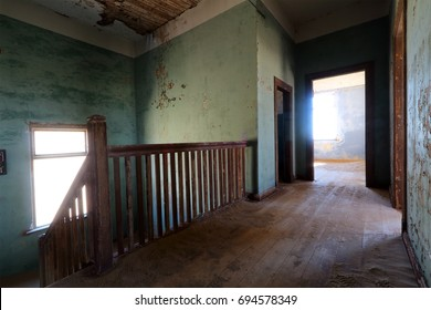 Eerie interior of an abandoned house with a passageway and staircase.
