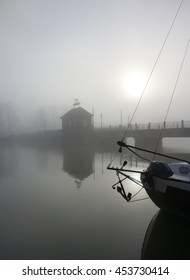 Eerie landscape with a bridge over a river in fog with sail boat silhouette in front