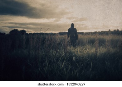 An eerie lone hooded figure standing in a field looking at the sunset. With a grunge, retro edit.