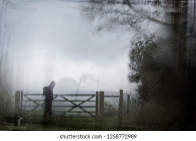 An eerie silhouette of a lone hooded figure with a rucksack by a gate surrounded by trees. With a dark, spooky blurred abstract, grunge effect edit.