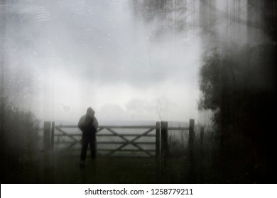 An eerie silhouette of a lone hooded figure by a gate surrounded by trees. With a dark, spooky blurred abstract, grunge effect edit.