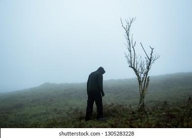 An eerie spooky figure standing by a tree on a foggy winters hillside
