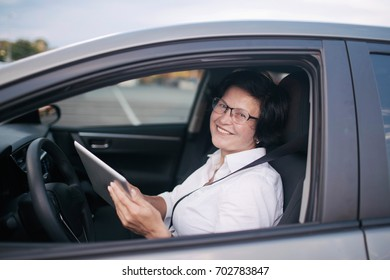 Effective business woman against a background of a car.