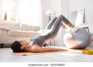 Effective exercises complex. Slender young woman doing torso lifts with the help of the fitness ball while doing morning calisthenics