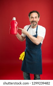 Effective product that works well. Eldery household worker presenting laundry detergent. Mature man pointing at detergent bottle. Senior man in apron ready for doing laundry. Household laundering.