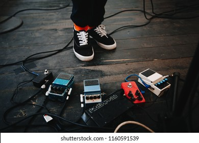 Effects unit with pedals and compressors for guitar legs of a man in sneakers on a background