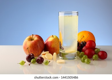 Effervescent soluble tablet of vitamins in a glass with water. Various fruits, a set of vitamins.