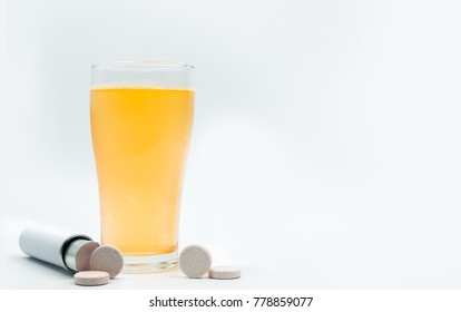 Effervescent tablets tube with blank label and orange effervescent bubbles of calcium and vitamin C in transparent glass. Vitamins, minerals and supplement concept.