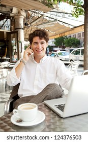 Efficient businessman making a call on his smart phone and using a laptop computer while sitting at a coffee shop terrace table, outdoors.