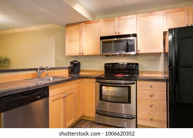 Efficient, compact kitchen design with honey stained kitchen cabinets with granite countertops, black refrigerator, Stainless steel kitchen appliances and tile flooring. Northwest, USA