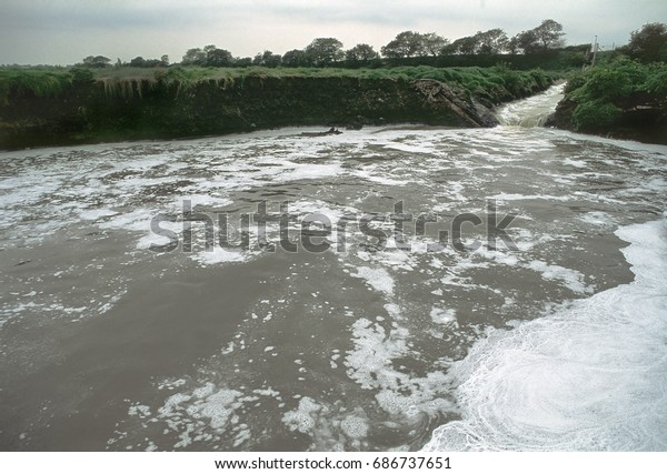 Effluent from sewage works flowing into the river, UK