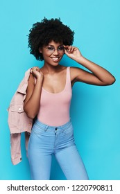Effortless beauty. Attractive young African woman smiling and looking at camera while standing against blue background
