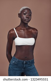 Effortless beauty. Attractive young African woman looking at camera while standing against brown background
