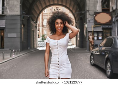 Effortless beauty. Attractive young Afro American woman in short white dress playing with hair and smiling