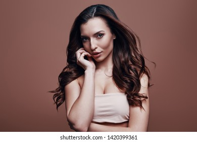 Effortless beauty. Attractive young woman looking at camera while standing against grey background