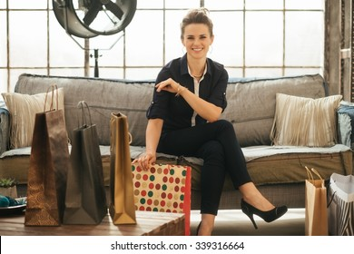 Effortlessly stylish brunette woman with multi-coloured shopping bags sitting on sofa in modern loft apartment. Good shopping spree makes any woman happy. Luxurious life concept
