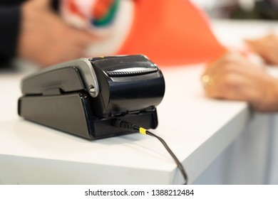 Eftpos machine at the counter with hands of customer who is buying the a good