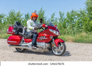 Eger, Hungary - July 04, 2019: Motor biker at red Honda Goldwing making a drive through Hungary between Budapest and Eger