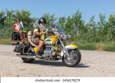 Eger, Hungary - July 04, 2019: Senior motor biker with beard and short pants at yellow Honda Goldwing making a drive through Hungary between Budapest and Eger