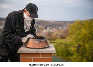 EGERSZOLAT, HUNGARY, Nov 2015 : A chimney sweeper on the rooftop of a house checking a smoking chimney. Illustrative editorial.