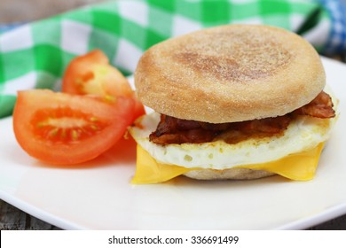 Egg and bacon muffin with tomatoes on the side
